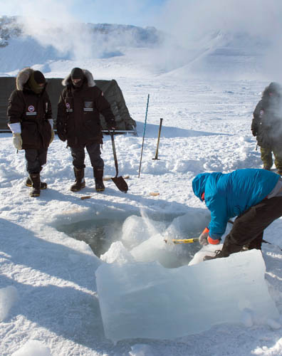 Ranger Absalem Kalluk Idlout of Resolute Bay uses an axe to break a 5-foot  (1.5m) long chunk of ice in half Photos: © 2014 DND-MDN Canada